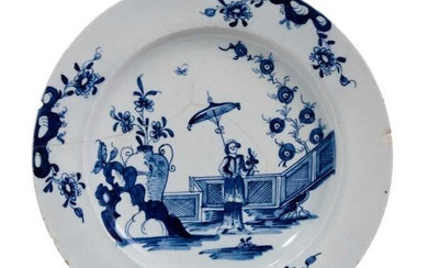 A good Lowestoft blue and white plate c.1770, painted with a Chinese lady holding a parasol, standing before a zigzag fence, the rim with three vignettes of prunus issuing from rockwork, 23cm