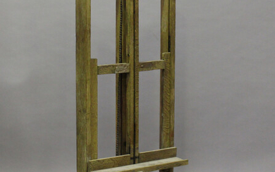 A mid-20th century limed oak artist's easel with chain-driven rising mechanism, height 165cm, w