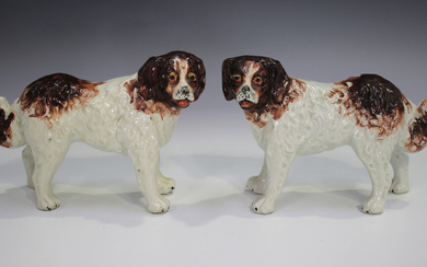 A pair of Staffordshire pottery models of St Bernard dogs, late 19th century, modelled standing with