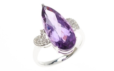 AN 18CT WHITE GOLD AMETHYST AND DIAMOND RING; centring a pear cut chequerboard amethyst of 4.91ct, between upswept shoulders set wit...