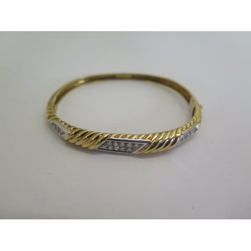 An 18ct yellow gold and white metal diamond bangle, 6.5x5.5c...