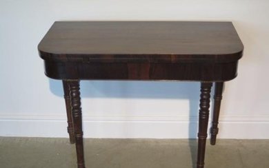 A 19th century rosewood fold over card table on turned suppo...