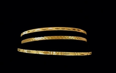 A CHARGED Three 18K (750°/°°) yellow gold bracelets chased with geometric motifs.