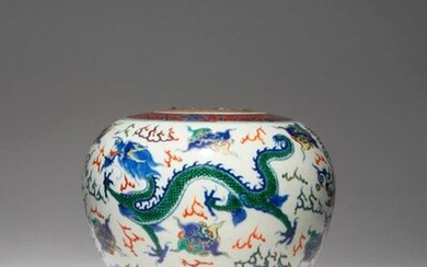 A CHINESE WUCAI 'DRAGON' VASE 19TH CENTURY The ovoid body brightly painted with two scaly dragons in flight over crashing waves, the mythical beasts divided by lotus sprays and stylised characters, with iron-red bands of floral motifs encircling the...