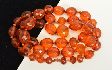 A FACETED AMBER BEAD NECKLACE, designed as oval and spherica...
