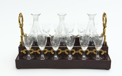 A FRENCH WOODEN AND GILT BRONZE 3 BOTTLE AND 12 GLASS TABLE TANTALUS - STOPPERS MISSING, 31 CM WIDE, 16.5 CM HIGH, 21 CM DEPTH, LEON...