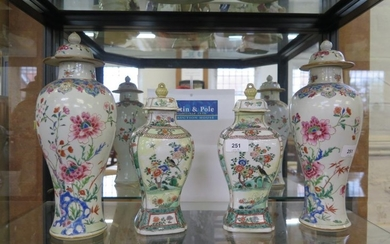 A pair of famille rose baluster vases and covers, with chrys...