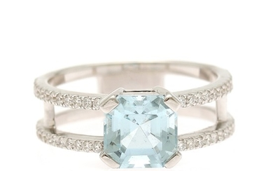 An aquamarine and diamond ring set with an emerald-cut aquamarine flanked by numerous brilliant-cut diamonds, mounted in 18k white gold. Size 51.
