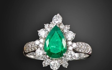 An emerald and diamond cluster ring, set with a pear-shaped emerald within a surround of graduated round brilliant-cut diamonds, with pave-set diamond shoulders in white gold, 18ct London hallmarks, size W 1/2