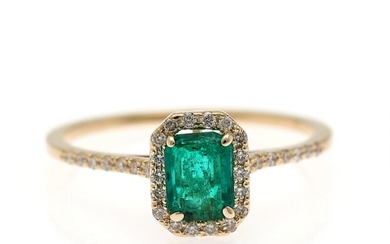 An emerald and diamond ring set with an emerald weighing app. 0.54 ct., encircled by numerous brilliant-cut diamonds, mounted in 14k gold. Size 52.