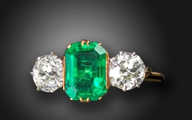 An emerald and diamond three-stone ring, the emerald-cut emerald is claw set with an old circular-cut diamond to each shoulder, with scroll pierced decoration to the gallery and trifurcated shoulders in platinum and gold, diamonds approximately 2.00cts...