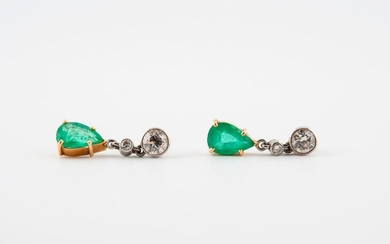 Pair of yellow gold (750) and platinum (850) earrings adorned with two brilliant-cut diamonds in a closed setting and holding a drop-cut emerald in pendulum shape.