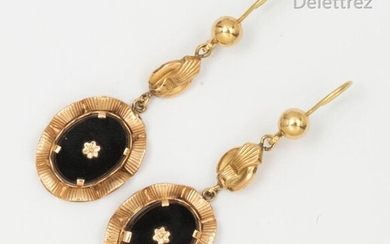 Pair of yellow gold earrings, holding a stylized flower by an oval onyx plate in an animated gadrooned surround. Length: 5.8cm. Gross weight: 7.9g.