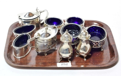 A collection of silver condiment items, comprising: a plain oval...
