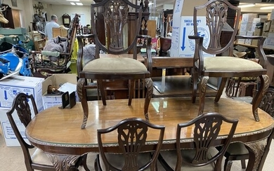 A glazed top mahogany dining table with carved legs and a se...
