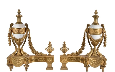 A pair of French gilt bronze and white marble mounted chenets in Louis XVI style