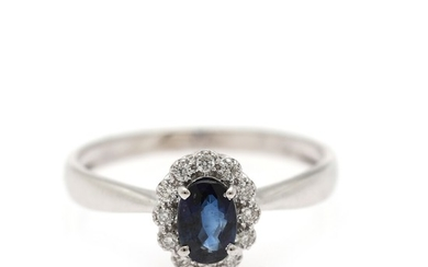A ring set with an oval-cut sapphire weighing app. 0.62 ct. encircled by numerous diamonds weighing app. 0.11 ct., mounted in 18k white gold. Size 54.