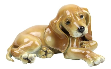 Allach Lying dachshund puppy, designed by Theodor Kärner (Hohenberg a. d. Eger 1884-1966 Munich), manufactured by Porzellanmanufaktur Allach, slightly cream-coloured porcelain, naturalistically painted under glaze, L 17 cm, H 9.5 cm, with green...