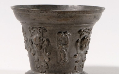 Mortar made of bronze with a scaled decoration of four heads of winged angels alternating with two busts of the pope in profile and two allegorical figures. Period XVIIe siècle. An eight-sided marble base is attached to it. H : 10,5 cm and D. sup :...