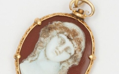 Yellow gold pendant with openwork volutes and foliage, decorated with a cameo representing a young man in bust glued on an agate plate. Length : 3,5cm. Weight : 6,1g.