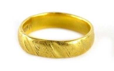 A 22ct gold wedding band, of polished and etched design, wit...