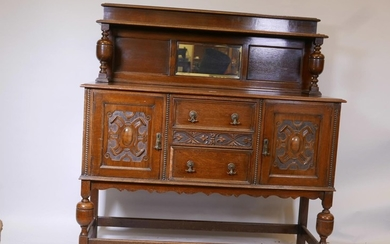 A Jacobean style oak sideboard, with inset mirror back top a...