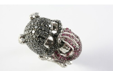 A RUBY AND DIAMOND NOVELTY DRESS RING in the form of a skull...