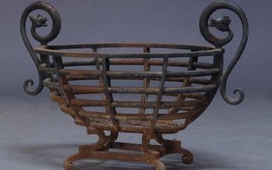 A cast iron fire basket, early 20th century, of oval...