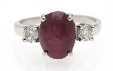 A ruby and diamond ring set with a cabochon star ruby flanked by two diamonds, mounted in 14k white gold. Size 51.