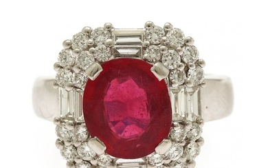 A ruby- and diamond ring set with an oval-cut ruby weighing app. 2.80 ct. encircled by numerous baguette and brilliant-cut diamonds, mounted in 18k white gold.