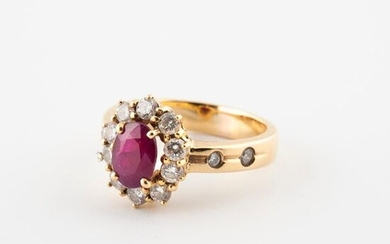 A yellow gold (750) daisy ring centered on an oval faceted ruby in a setting of brilliant-cut diamonds in claw setting.