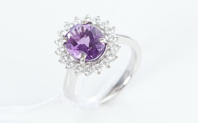 AN AMETHYST AND DIAMOND CLUSTER RING IN 18CT WHITE GOLD, THE OVAL CUT AMETHYST WEIGHING 2.45CTS, WITHIN A SURROUND OF DIAMONDS TOTA...