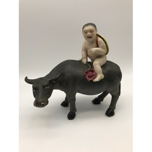 An Antique Chinese porcelain nude boy figure riding on top o...