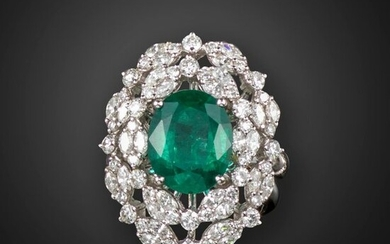 An emerald and diamond cluster ring, the oval-shaped emerald is set within clusters of marquise and circular-cut diamonds in white gold, size N
