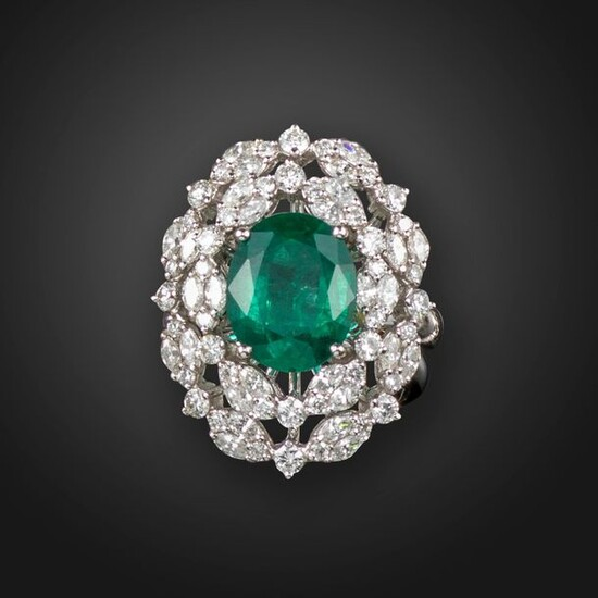 An emerald and diamond cluster ring, the oval-shaped emerald is...