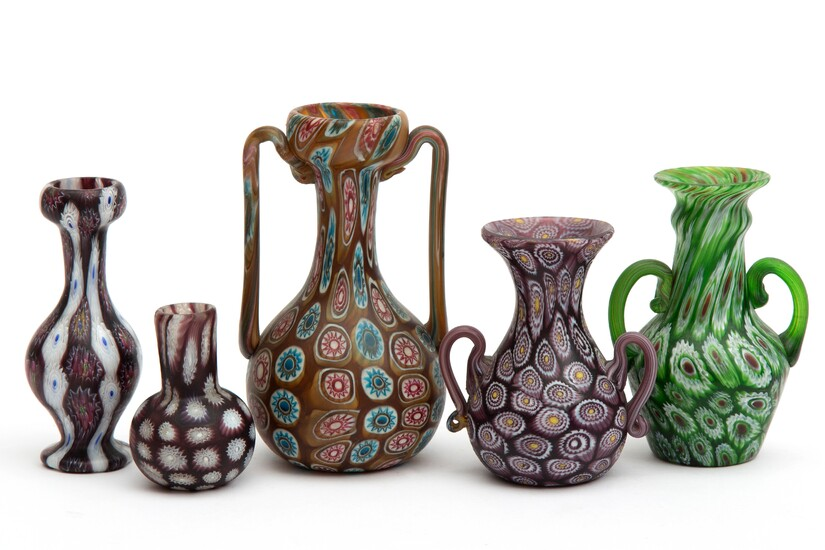 Five glass vases in the millefiori style, produced by the firm Fratelli Toso; left to right, the vases are: cranberry red with blue-centered white flowers in vertical stripes; cranberry red with white flowers; with handles, caramel colored, with red-on-white and cerulean-on-white flowers; with handles, cranberry red with yellow-centered white flowers; with handles, grass green with red-centered white flowers.
