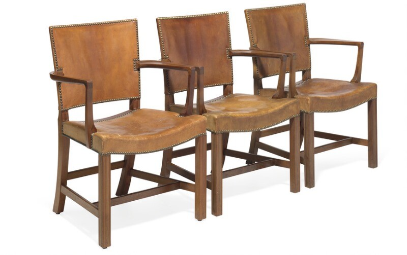 """Kaare Klint: """"The Red Chair"""". Three armchairs with profiled Cuban mahogany frame. Upholstered with patinated Niger leather, fitted with brass nails. (3)"""