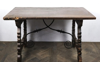 Moulded and carved wood table, wrought iron spacer.