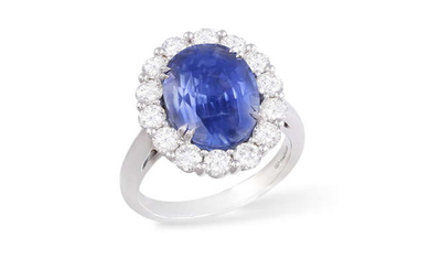 A SAPPHIRE AND DIAMOND CLUSTER RING The oval-shaped...