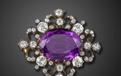 A Victorian amethyst and diamond-set brooch pendant, centred with an oval-shaped amethyst, with graduated circular-cut diamonds to the scroll mount in silver on gold, detachable brooch fitting, 4cm wide, case by Harvey & Gore