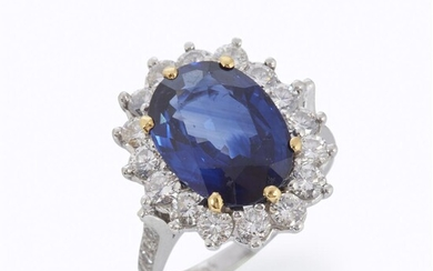 A sapphire, diamond, and platinum ring centering an oval-cut...