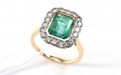 AN EMERALD AND DIAMOND CLUSTER RING IN 18CT GOLD, EMERALD WEIGHING 3.33CTS, SIZE P