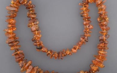 An Amber Necklace, ninety-five irregular shaped and sized orangey-brown amber...