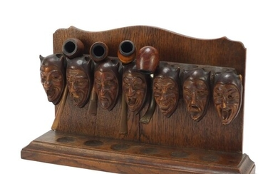 Carved oak devil head design pipe stand with four pipes incl...