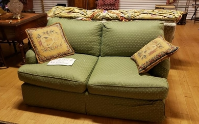 Green upholstered love seat with 2 embroidered pillows