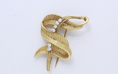 750-thousandths gold clip brooch, stylizing a leaf coiled...