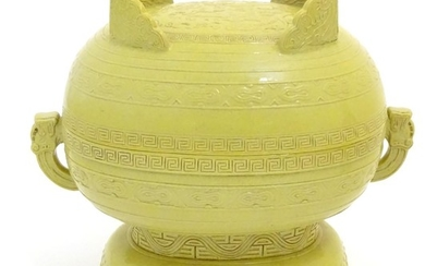 A Chinese yellow ground lidded pot raised on a foot, with tw...