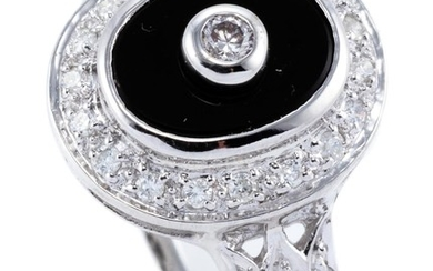 A DECO STYLE 9CT WHITE GOLD ONYX AND DIAMOND RING; oval onyx plaque centre set with a round brilliant cut diamond, to surround and s...