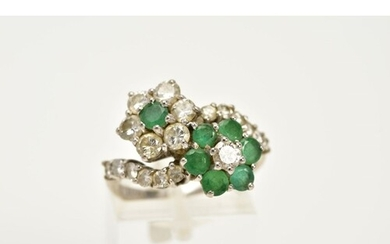 A DIAMOND AND EMERALD CROSSOVER RING, the white metal ring o...