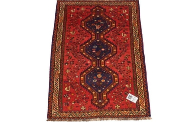 A TRIBAL PERSIAN SHIRAZ RUG. 100% wool. Hand-knotted village weave from the Fars province with tribal design of triple hooked medall...